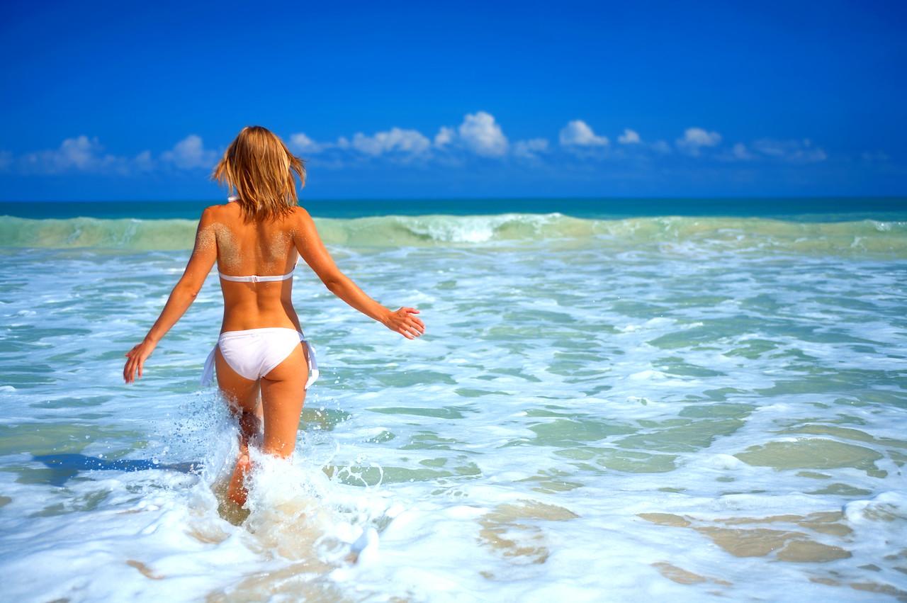 Beautiufl girl in a white bikini running into the ocean