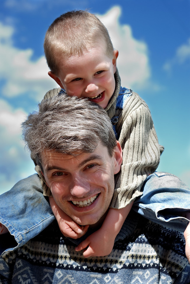 Little joyful boy sitting on the young man shoulders