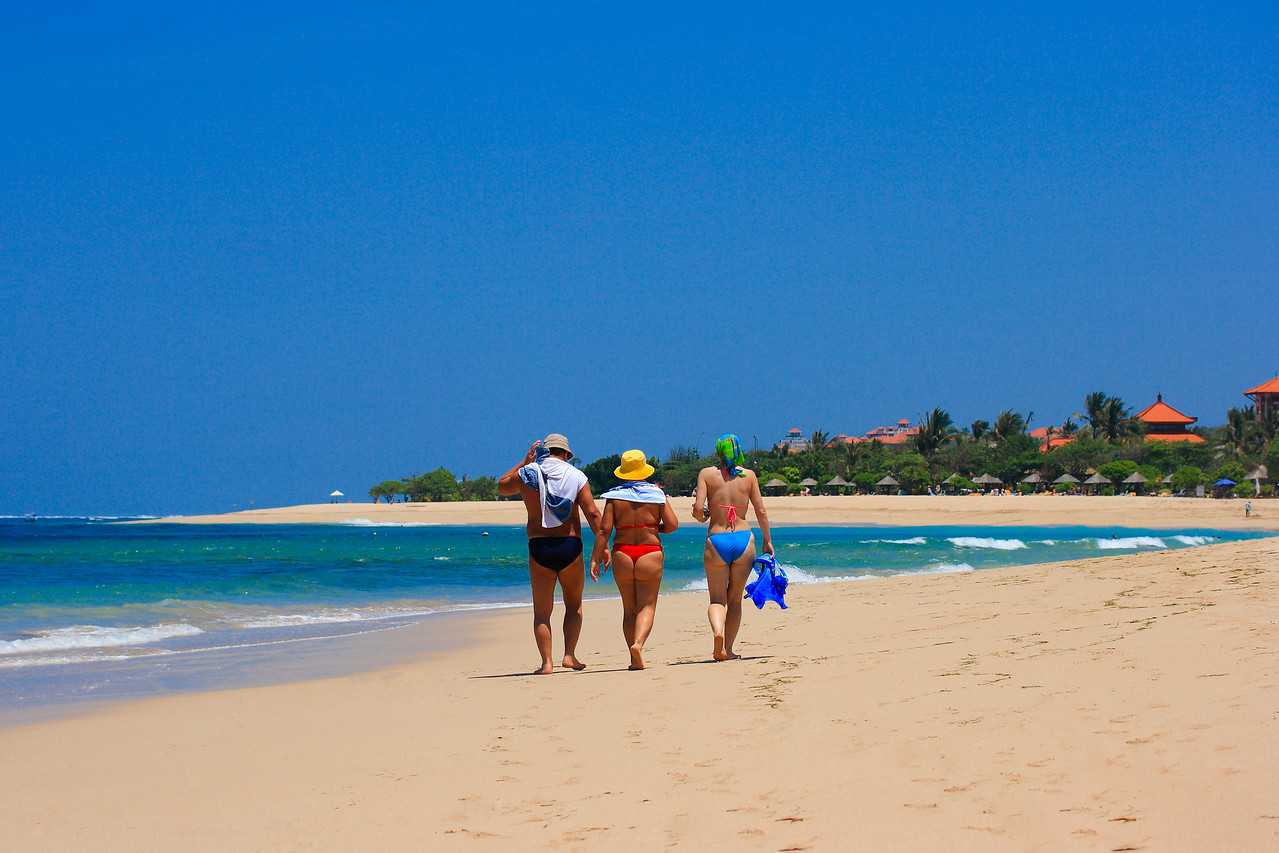 usual family (father, mother and daughter) walking along the beach