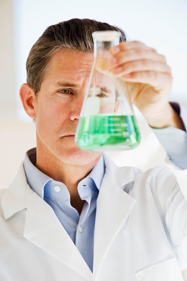 scientist holding up jar of chemicals