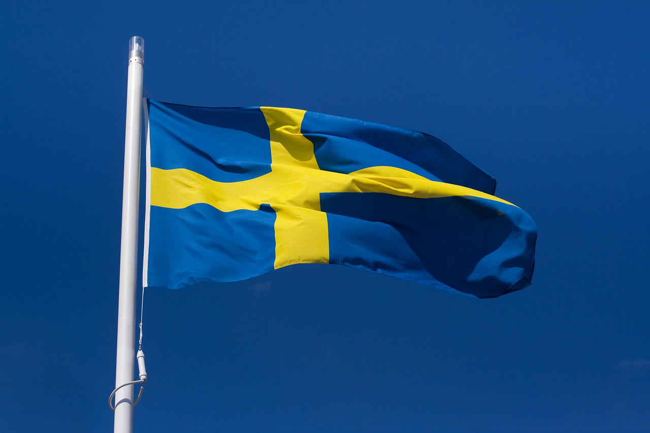 Waving flag of Sweden against the clear blue sky