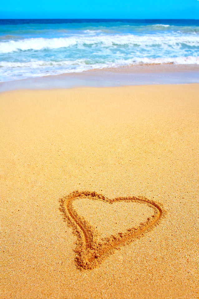 This is a photograph of a heart scratched into a beautiful empty beach in Hawaii. It is a perfect shot for a background.