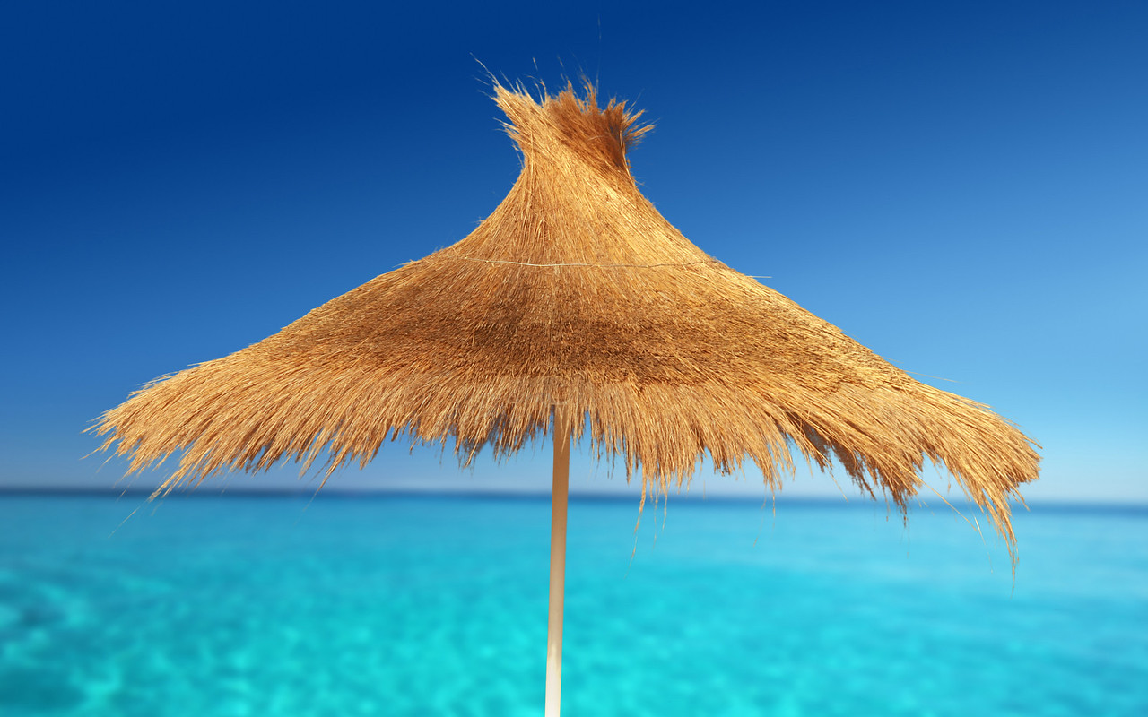 Relaxing on Tropical Beach under umbrella on sunny day