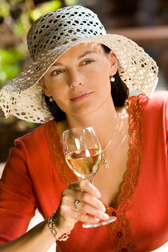 A beautiful young woman drinking a glass of white wine while bathed in summer sunshine