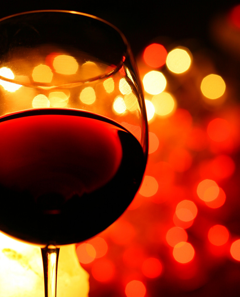 close-up of glass of red wine, with illuminated background