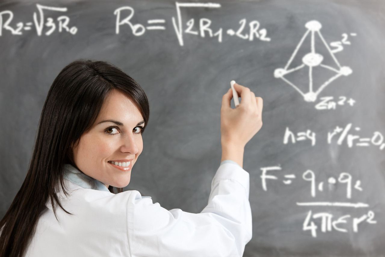 portrait of mid adult woman writing chemical formula on blackboard