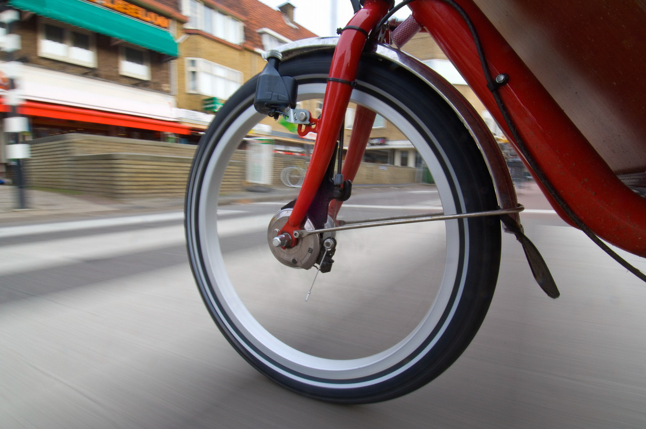 The spinning and vibrating wheel of a delivery bicycle on a suburban street