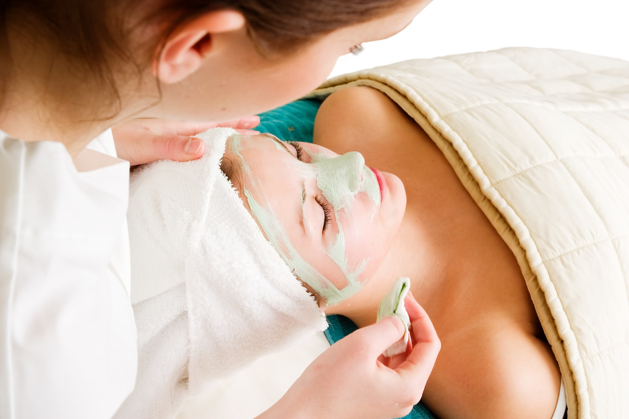 Detail of a facial mask treatment being wiped off the face.