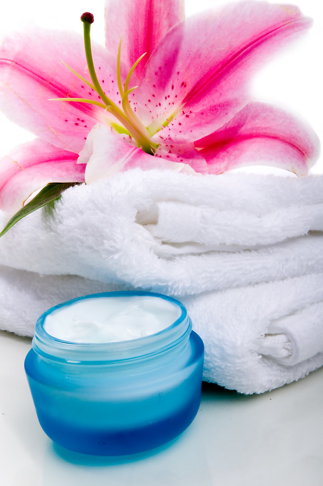Lilly flower on white towel  with face cream
