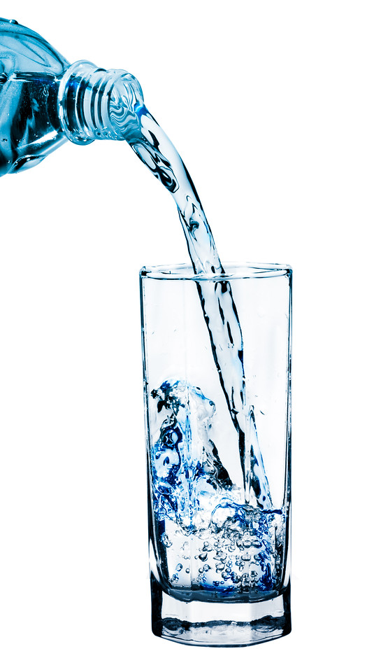Stream of clean water pouring from a bottle into a glass with a spray