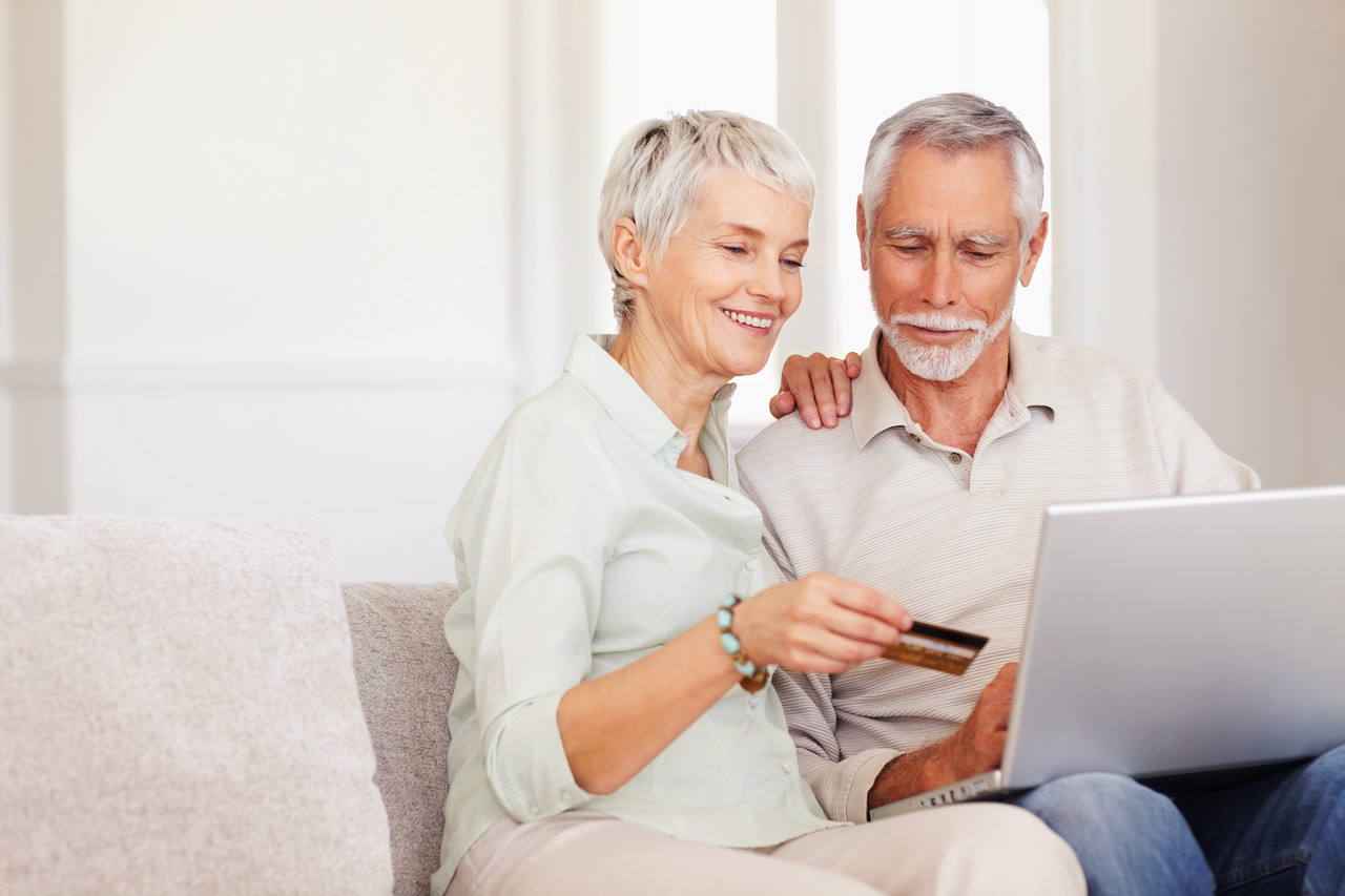 Happy senior couple using a laptop and a credit card to shop