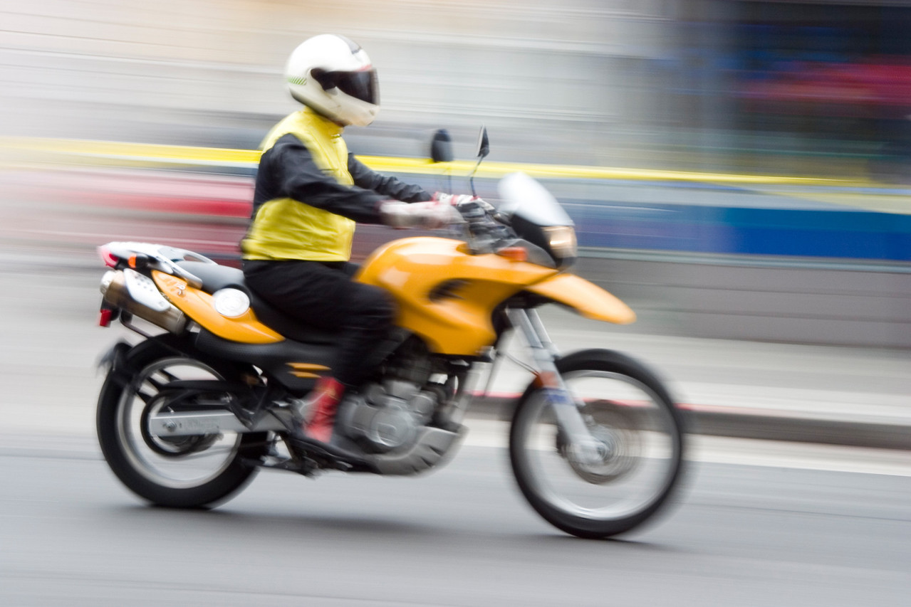 A speeding motorcycle with intentional camera motion blur.
