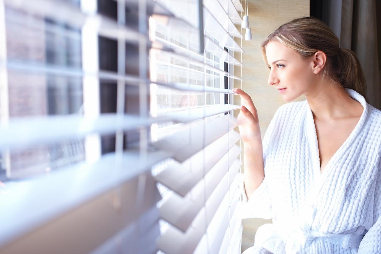 Young beautiful woman looking through window