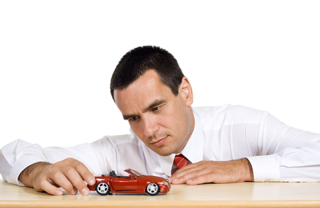 Businessman playing with a red toy car, dreaming - isolated