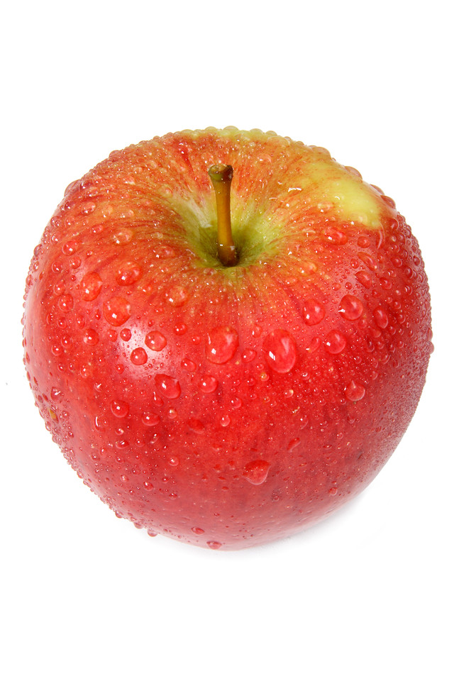 A freshly washed apple covered with droplets of water.