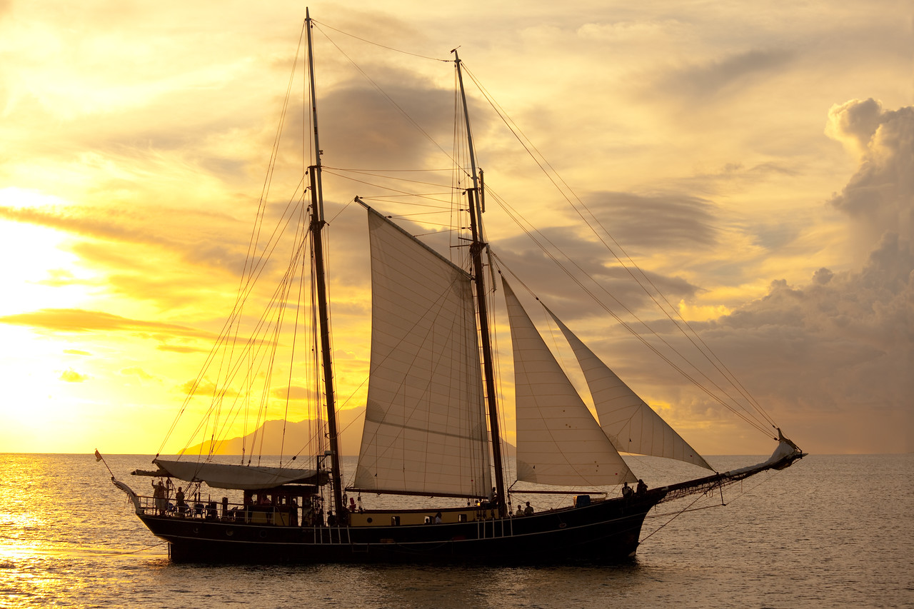 old sailing vessel on calm sea at sunset