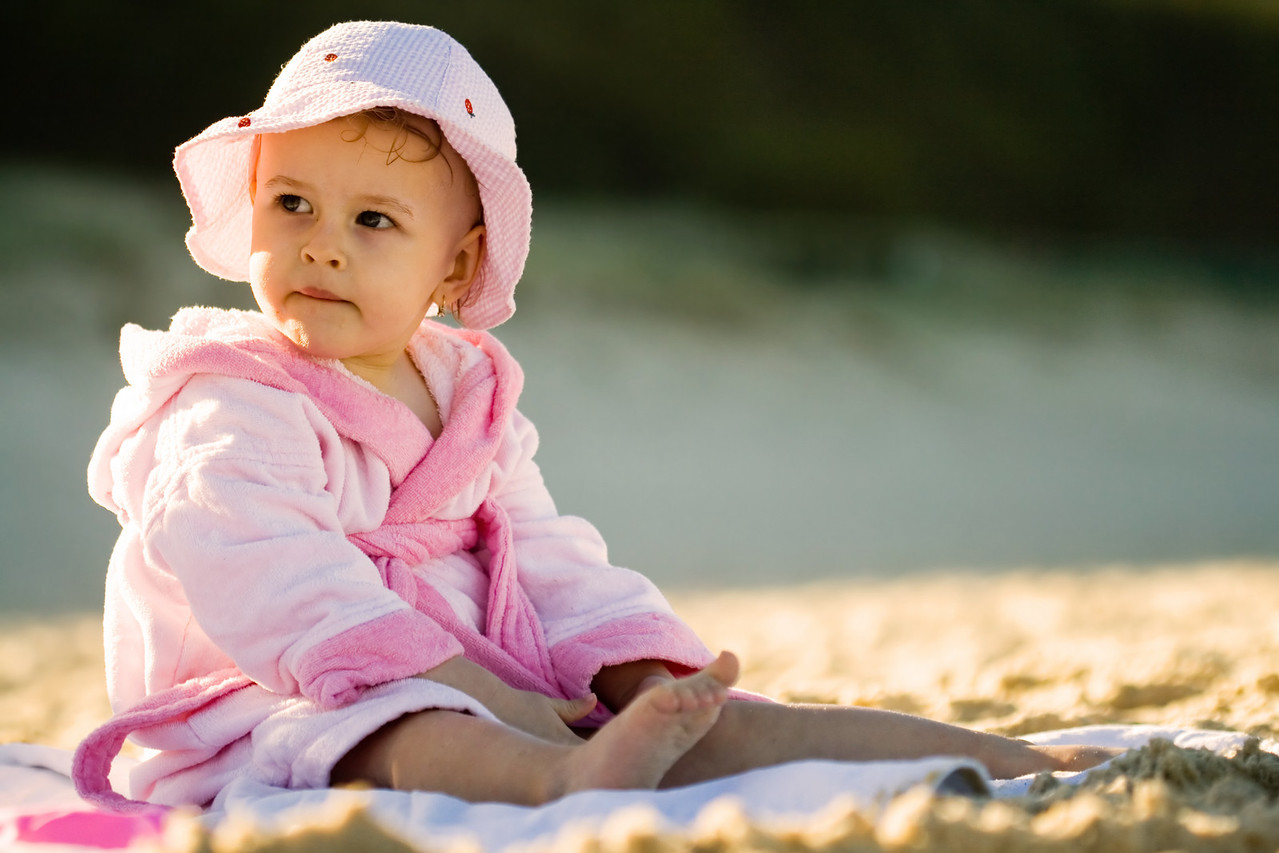 Baby girl in pink sitting on the beach