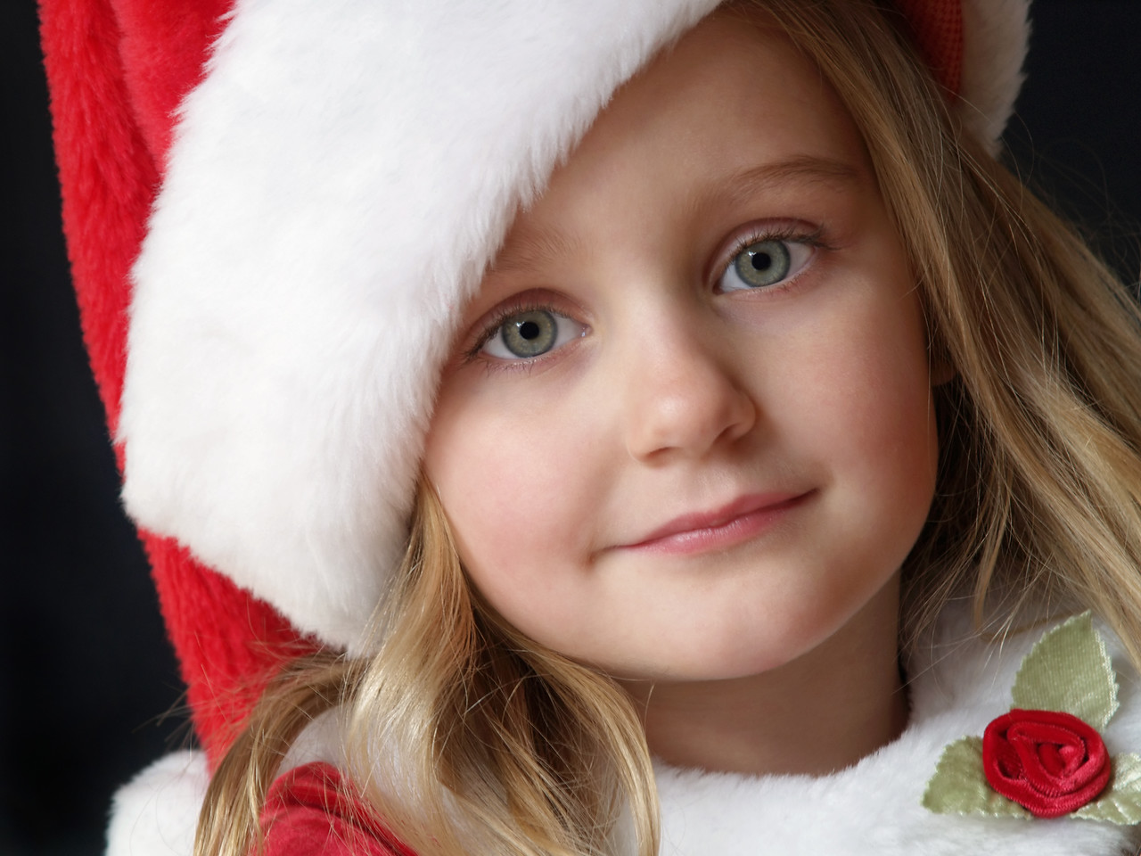 little girl wearing a Christmas dress and Santa hat
