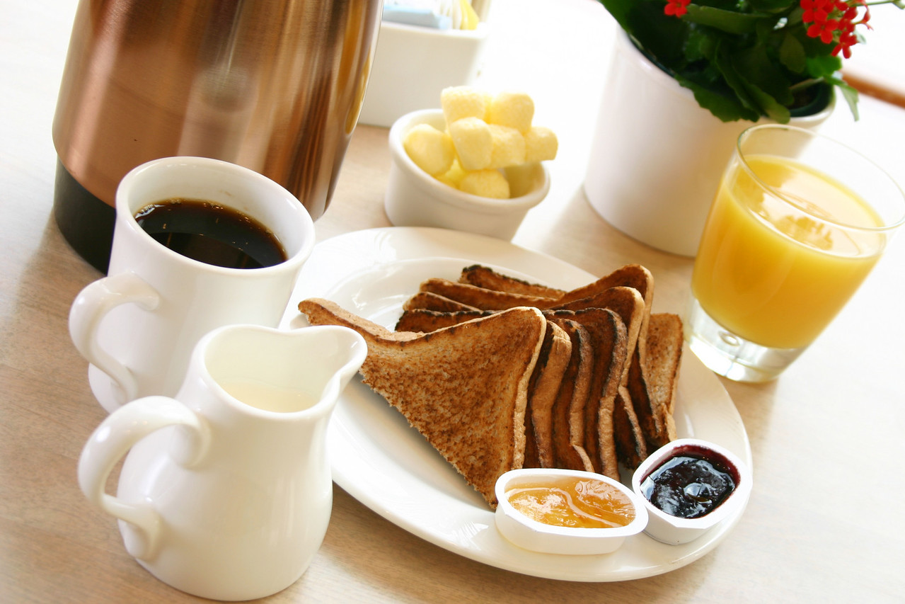 Classic breakfast of coffee, toast, butter and orange juice
