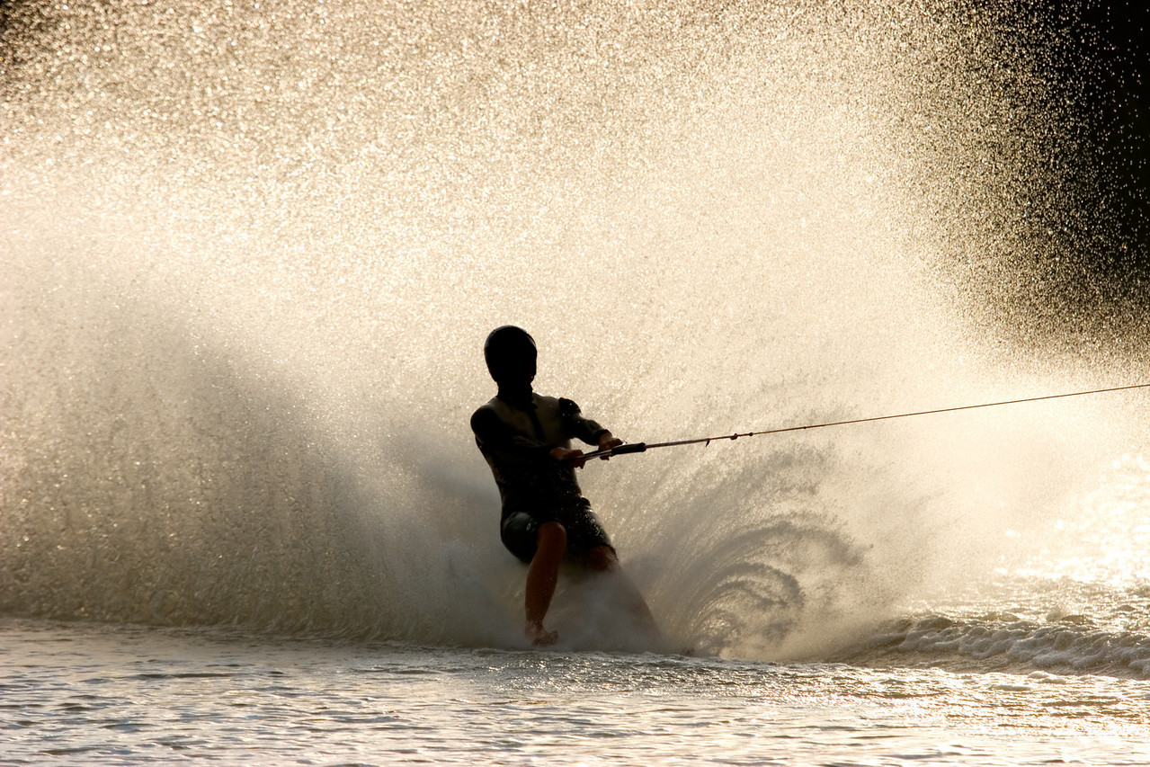 Silhouette of a barefoot water skier with backlit water spray
