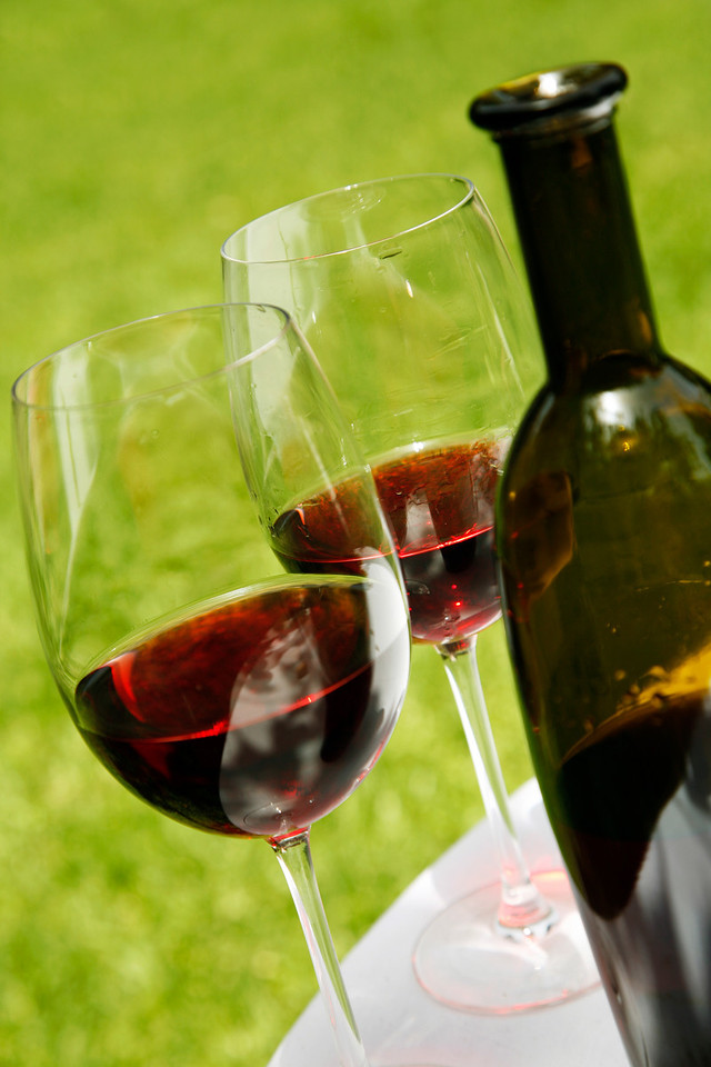 Red wine in glasses with bottle and green outdoor background