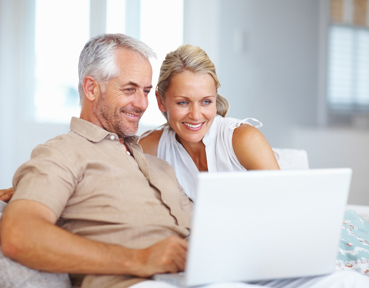 Portrait of an happy aged couple surfing on a laptop