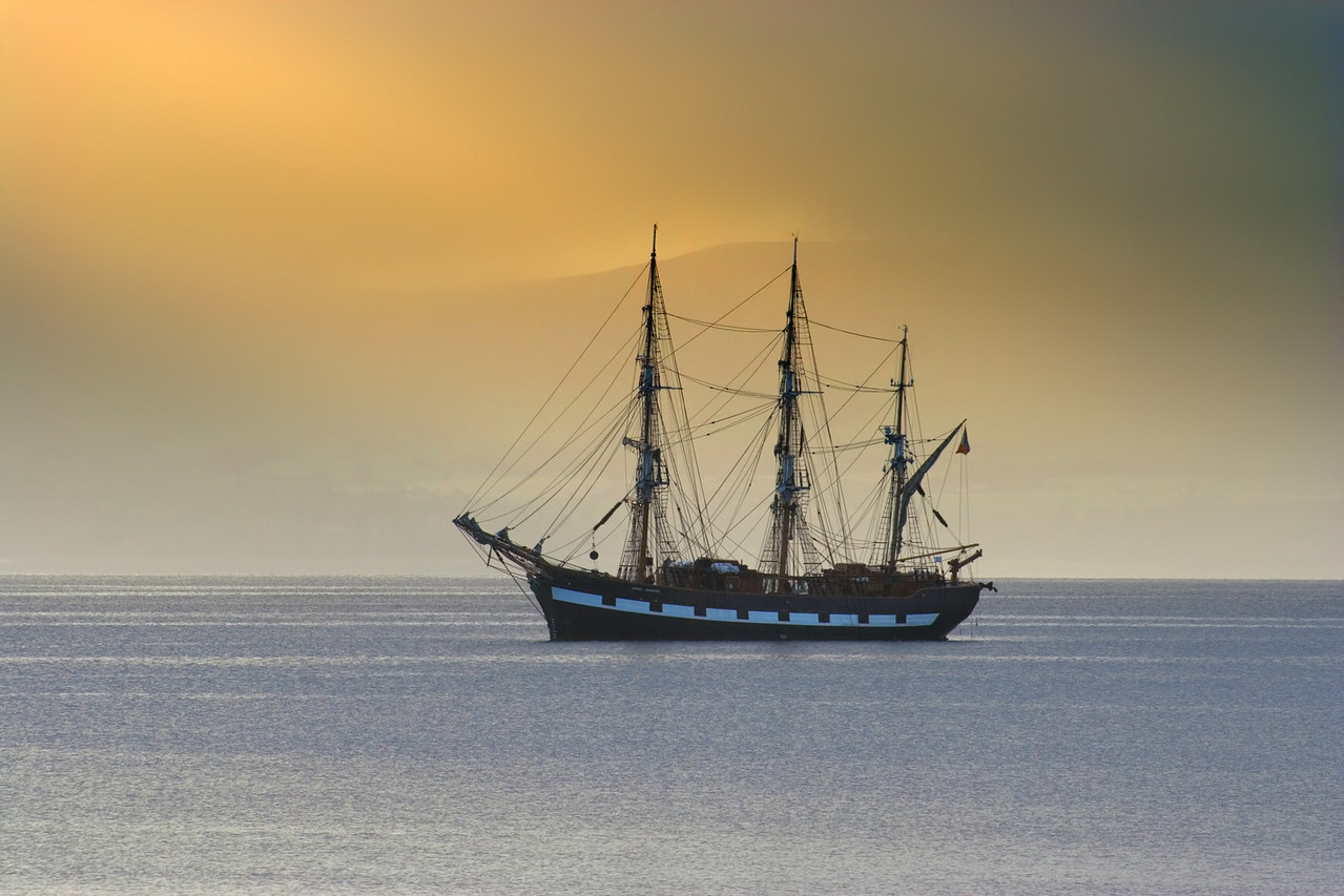Tall ship anchored in a calm sea lit by morning light