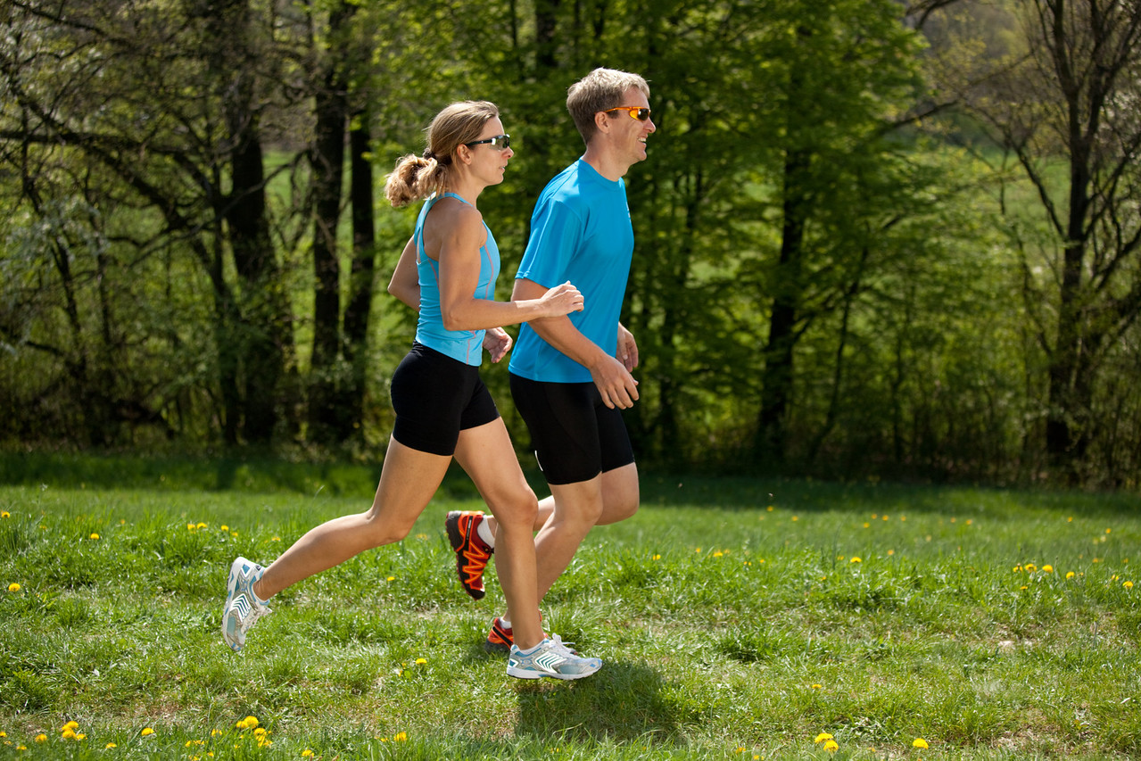 woman and man jogging together over meadow in springtime