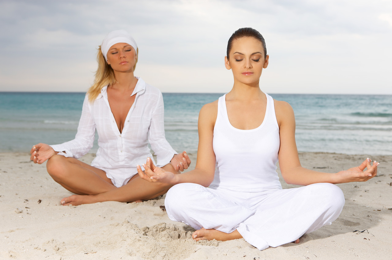 Two Young beautiful women during yoga on sea beach