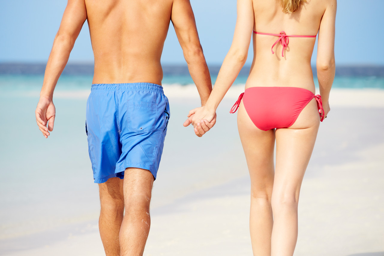 Close Up Of Romantic Couple Walking On Tropical Beach