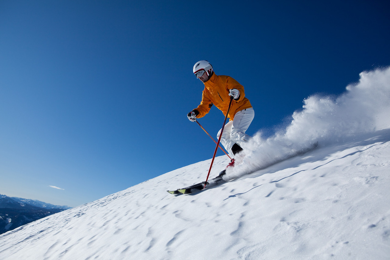 male skier enjoying skiing down fresh snow