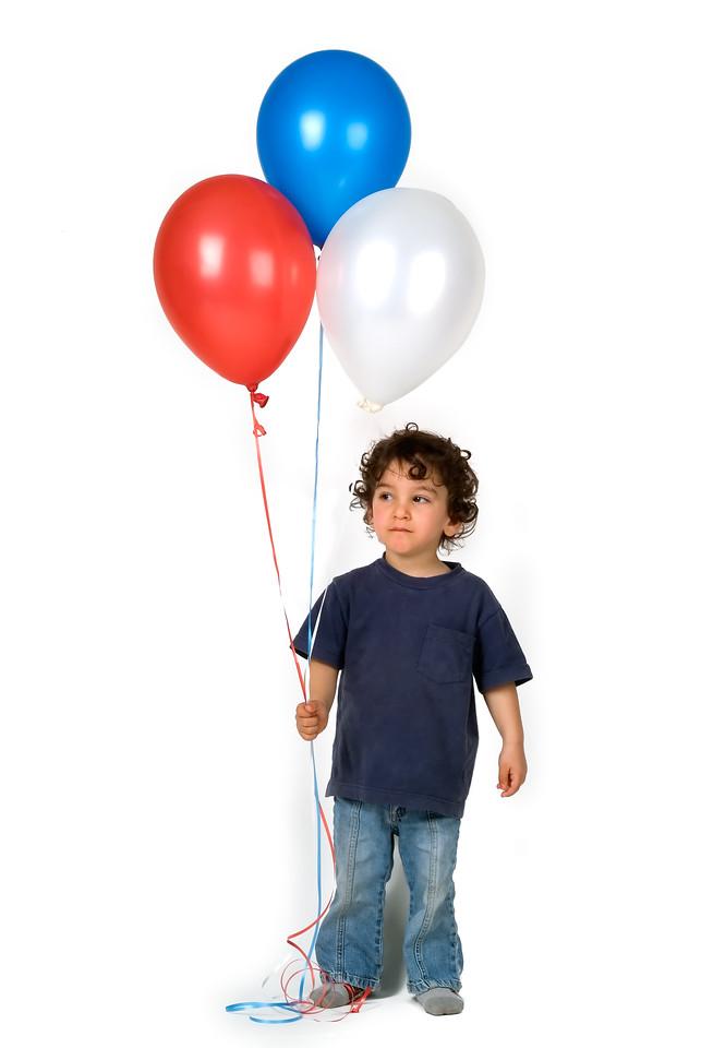 little boy holding 3 balloons
