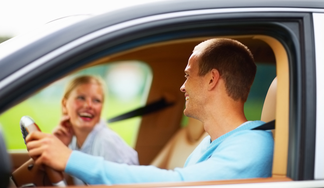 Young couple enjoying themselves while on a drive in a car