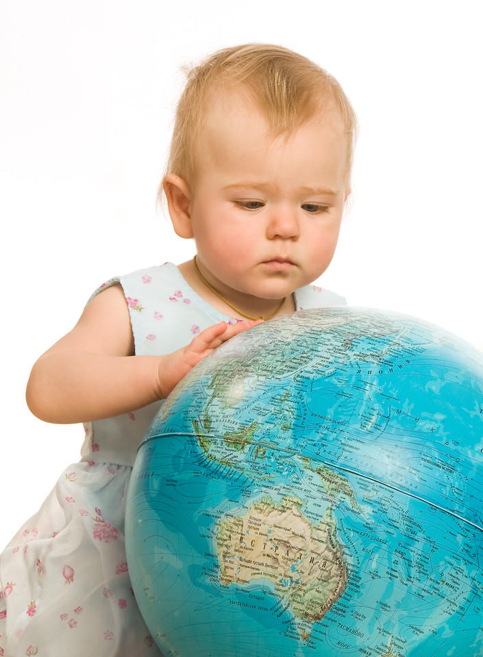 The little girl attentively examines the big globe on a white background