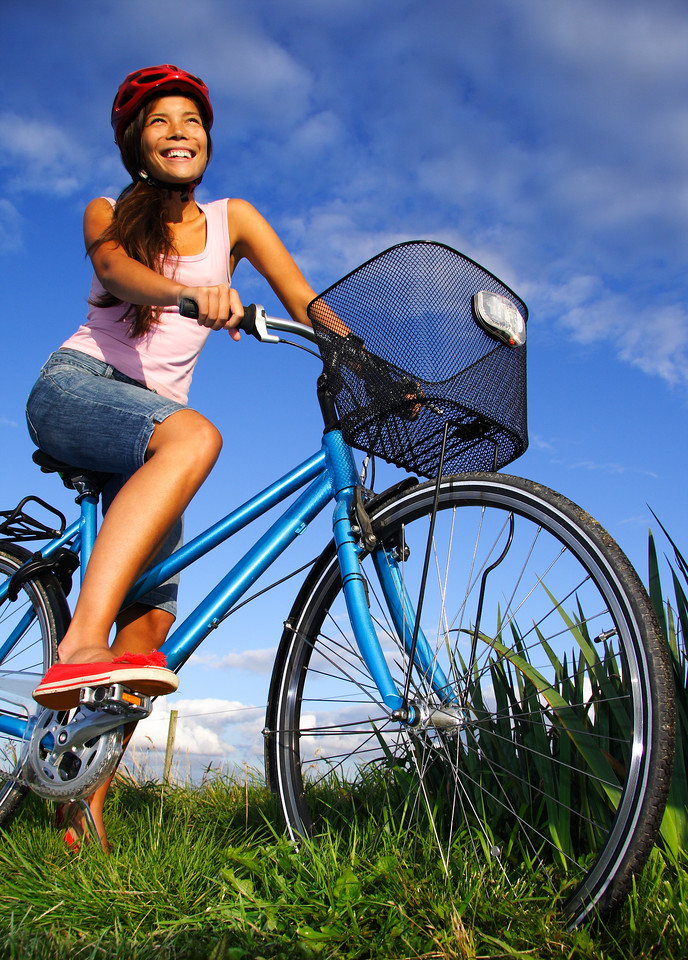 Woman biking under deep blue sky in the countryside of Jutland, Denmark during summer. Beautiful happy woman.