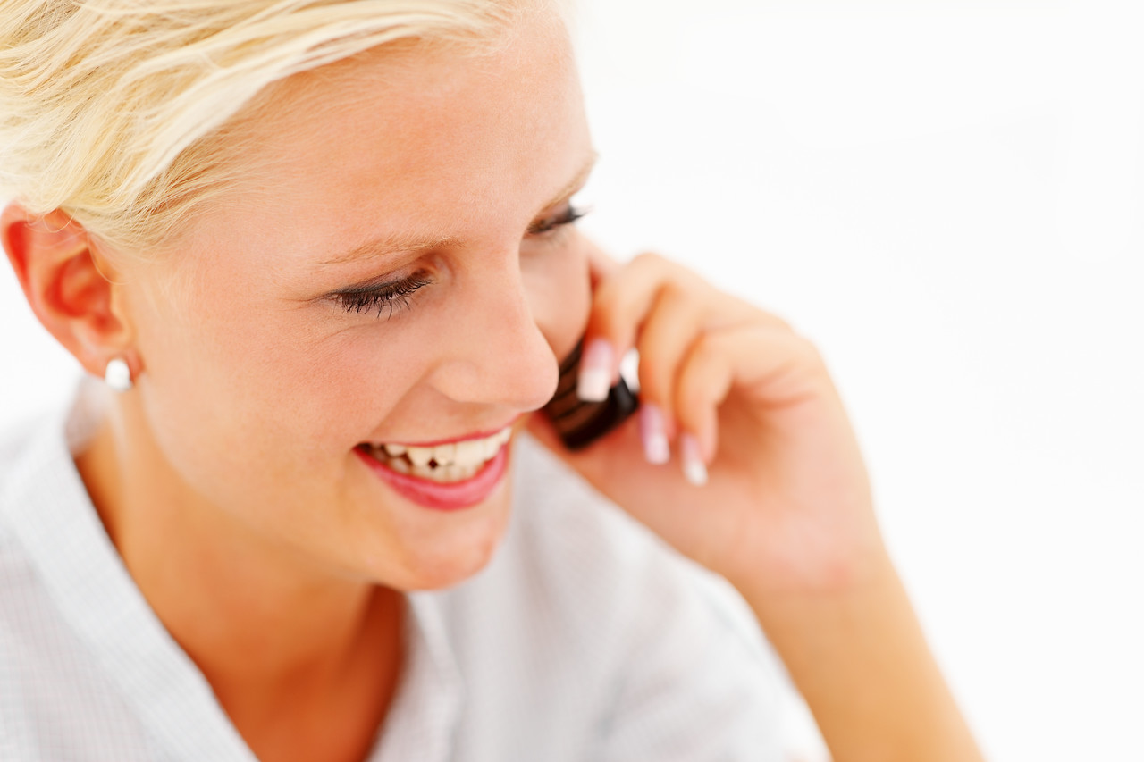 Closeup of a young female speaking on the cellphone isolated over white