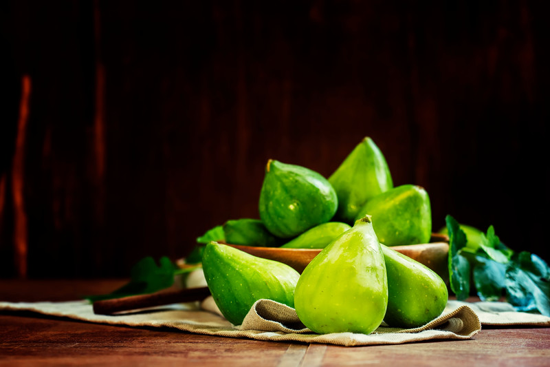 Sweet green figs in bowl, wooden background, selective focus