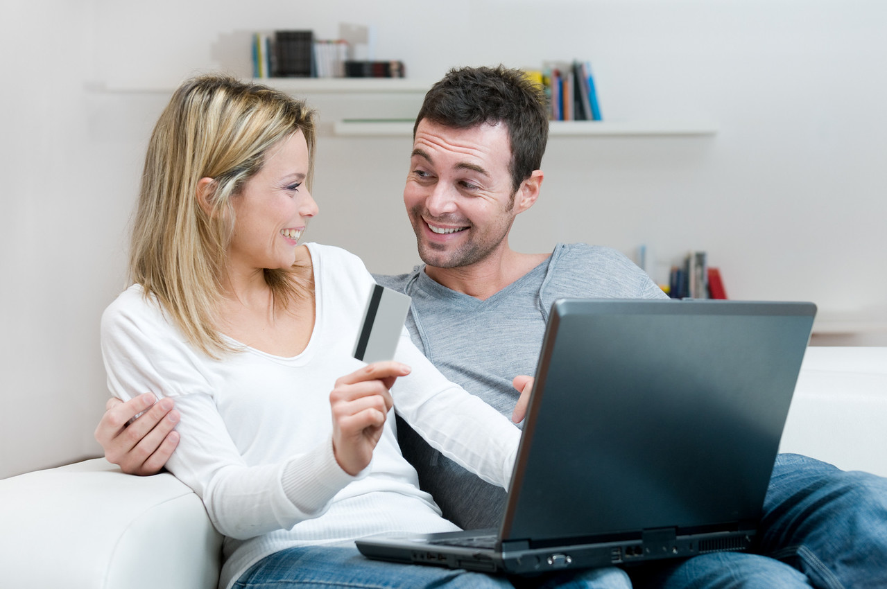 Young smiling couple making shopping online with credit card at home