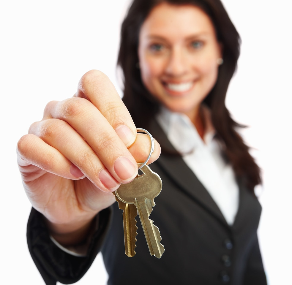 Business woman holding keys over white background