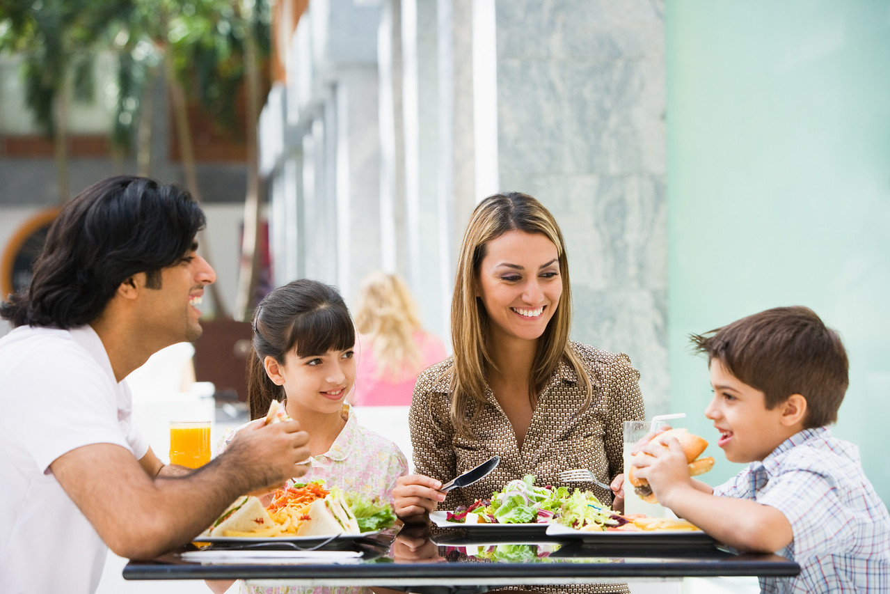 Family enjoying meal sitting at cafe table