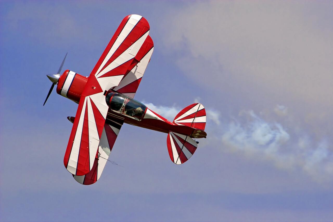 a red-white  biplane at an air show.