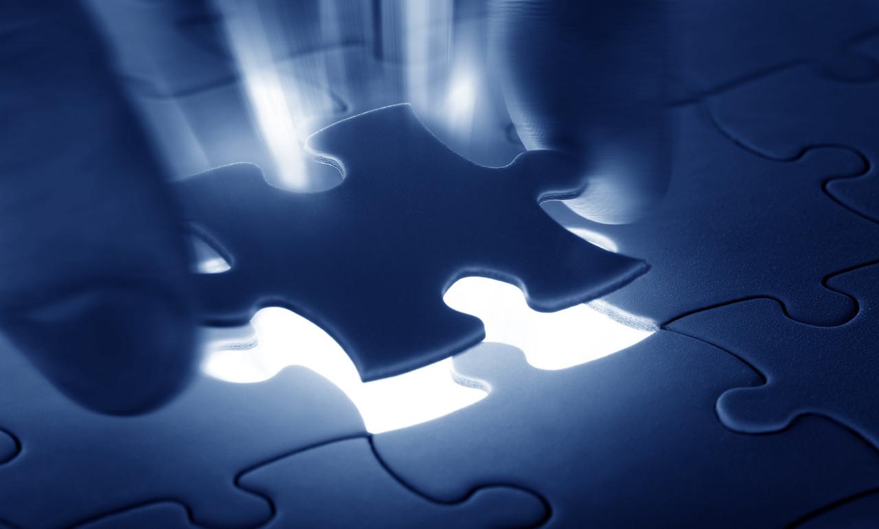 Hands placing last piece of a Puzzle