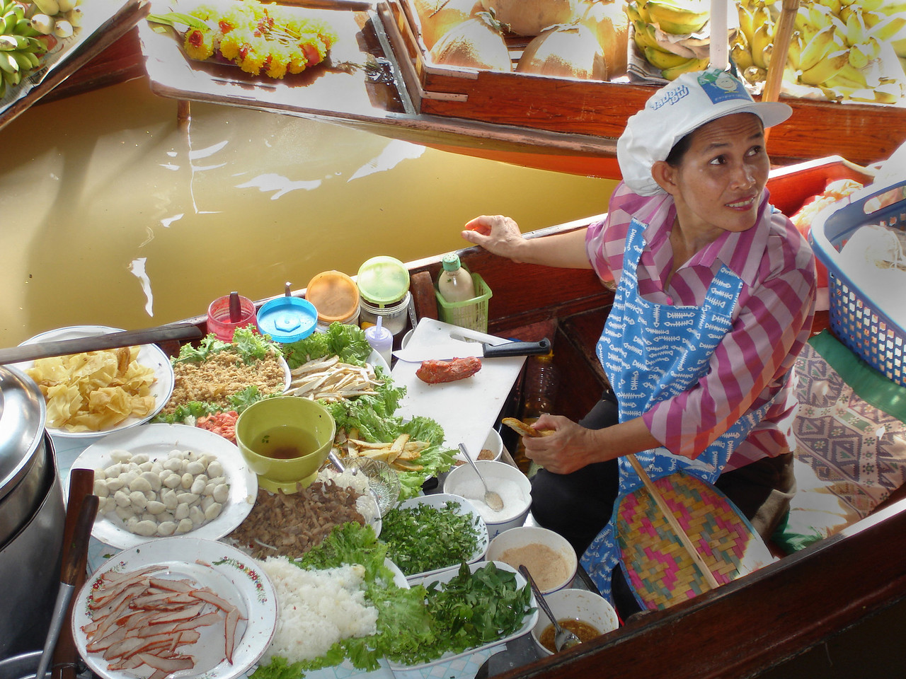 A Thai woman sells piping hot noodle soups from her small flat boat at one of the klongs (canals) at the famous floating market at Damnoen Saduak, west of Bangkok, Thailand