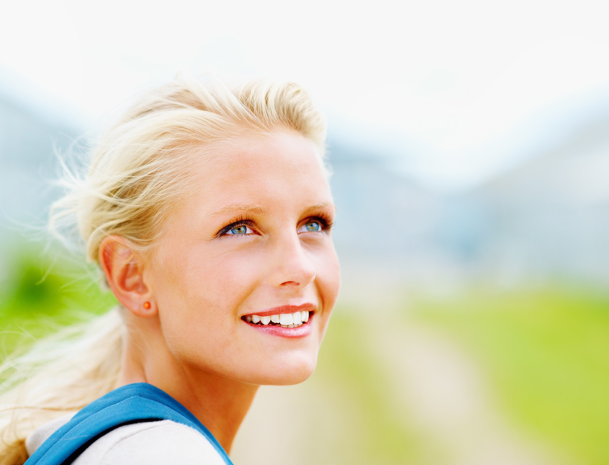 Pretty young blond female college student smiling outdoors , looking away