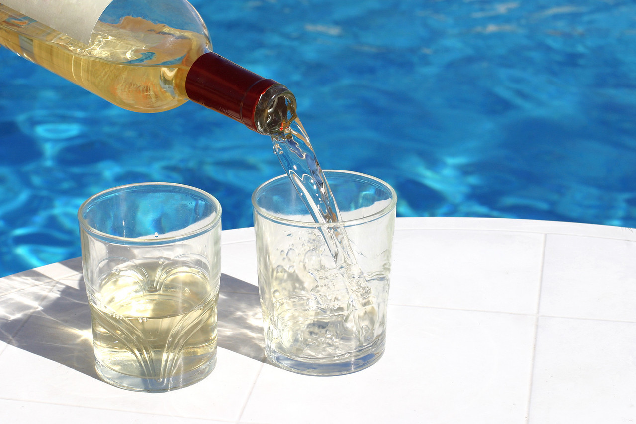serving 2 glasses of white wine at the swimming-pool
