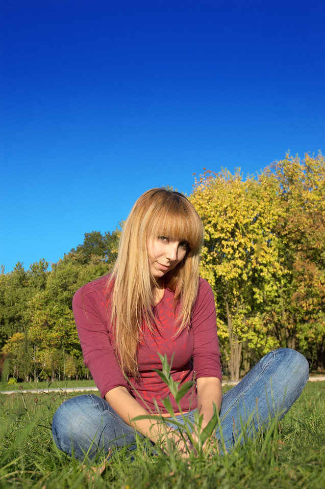slim shaped beautiful blond girl relaxing at park meadow