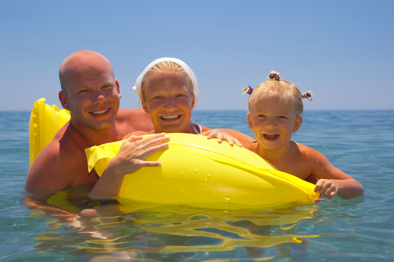 young family on air matrasse in water