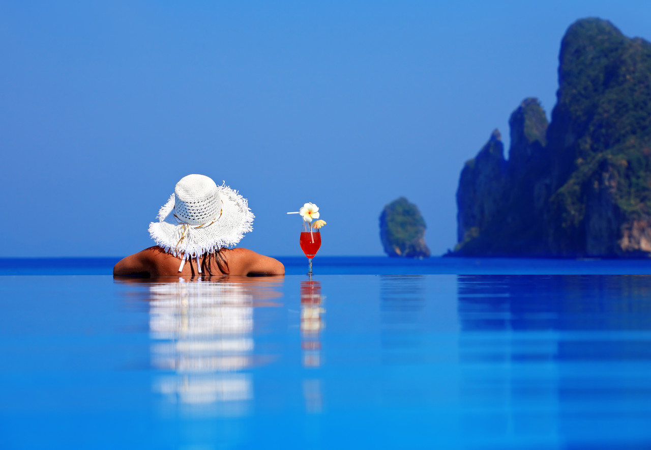 Rear view of the woman relaxing in pool with cocktail.(NOT photoshoped).