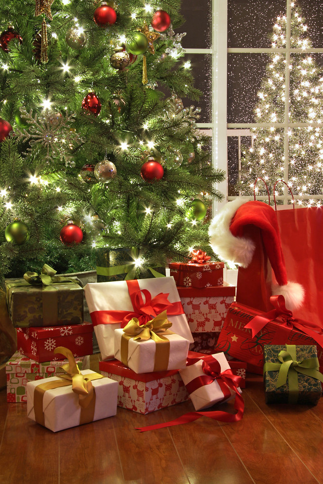 Brightly lit christmas tree with lots of gifts near window