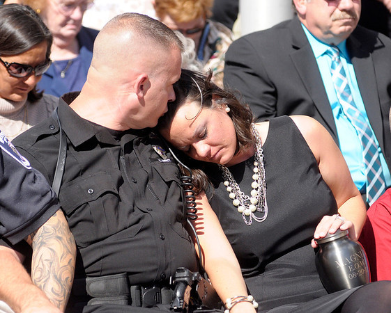 Matt Jarrett comforts his wife during the ceremony. K-9 officers live with their handlers and become a part of their family.